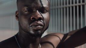 Überzeugter und verärgerter Afroamerikanermann, der die Kamera - im Freien betrachtet Drogenhändler, Gefangener oder kriminelle M stock video