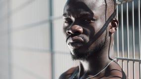 Überzeugter und verärgerter Afroamerikanermann, der die Kamera - im Freien betrachtet Drogenhändler, Gefangener oder kriminelle M stock video footage