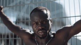 Überzeugter und verärgerter Afroamerikanermann, der die Kamera - im Freien betrachtet Drogenhändler, Gefangener oder kriminelle M stock footage
