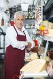 Überzeugter Verkäufer Standing At Counter im Käse-Shop Stockbild