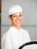 Überzeugter weiblicher Bäcker Holding Baking Tray Stockfoto