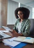 Überzeugter weiblicher Designer, der an einer digitalen Tablette arbeitet stockbild