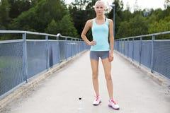 Überzeugter weiblicher Läufer, der ihren Bruch nachdem dem Laufen hat Stockfotografie