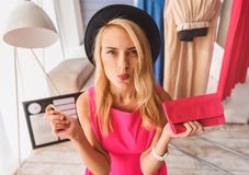 Überzeugter weiblicher Mode Blogger, der Handtasche darstellt Stockfoto