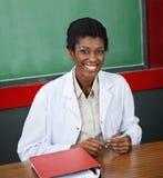Überzeugter weiblicher Professor Sitting At Desk stockfotos