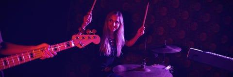 Überzeugter weiblicher Schlagzeuger, der Gitarristen bei der Ausführung am Stadium betrachtet stockfotografie