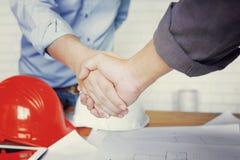 Überzeugter zwei Geschäftsmann, der Hände während einer Sitzung im Architektenbüro rüttelt stockfotos