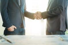 Überzeugter zwei Geschäftsmann, der Hände während nach einer Sitzung rüttelt stockfotos