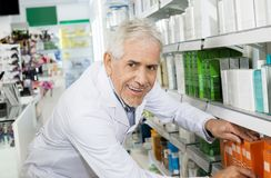 Überzeugtes Apotheker-Arranging Medicines On-Regal in der Apotheke Lizenzfreies Stockbild
