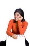 Überzeugtes asiatisches Mädchen in der orange Oberseite. Lizenzfreie Stockbilder