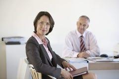 Überzeugtes Geschäftsfrau-With Colleague In-Büro Stockbild