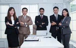 Überzeugtes Geschäftsteam, das in modernem Büro lo steht und lächelt Lizenzfreie Stockfotografie