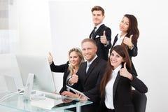 Überzeugtes Geschäftsteam, das sich Daumen zeigt Stockfoto