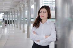 Überzeugtes junges asiatisches busineswoman, das einen Pfosten am Gehweg außerhalb des Büros lehnt FührerGeschäftsfraukonzept stockbild