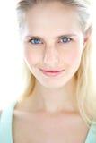 Überzeugtes junges blondes Frauenlächeln Lizenzfreie Stockfotografie