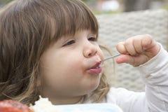 Überzeugtes Kleinkind, das mit Löffel isst Stockfotos