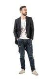 Überzeugtes lächelndes Mode-Modell mit den Händen in den Taschen, die weg schauen Lizenzfreie Stockbilder