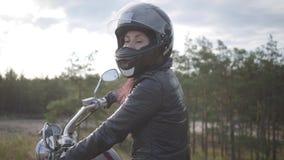 Überzeugtes Mädchen, das den schwarzen Sturzhelm sitzt auf dem Motorrad zurück schaut auf der Straße trägt Hobby, reisend und akt stock footage