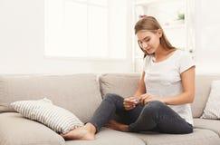 Überzeugtes Mädchen, welches die Ergebnisse ihres Schwangerschaftstests liest Stockfotografie