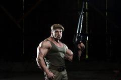 Überzeugtes Mann-Porträt mit Maschinengewehr Lizenzfreie Stockfotos