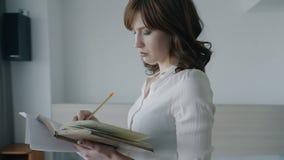 Überzeugtes schönes Geschäftsfrauschreiben im Notizbuch, das im modernen Büro steht stock footage