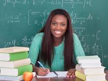 Überzeugtes Schreiben des weiblichen Lehrers im Buch am Klassenzimmerschreibtisch Lizenzfreies Stockfoto