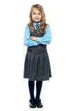 Überzeugtes Schulmädchen in der Kinderschürzeuniform Stockfotos