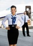 Überzeugtes Stewardess mit den Händen auf Hüfte am Flughafen Stockbild