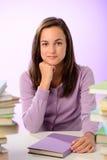 Überzeugtes Studentenmädchen zwischen Stapeln Büchern Stockbild