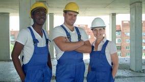 Überzeugtes verschiedenes Team von den Arbeitern und von Frauen, die in ihren Jeansstoffen und in Hardhats lächelnd an der Kamera stock video