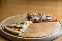 Übrig gebliebene Pizzastücke auf einem hölzernen Schneidebrett Stockbilder