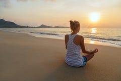 Übt Yoga im Sonnenaufgang Stockbild