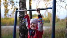 Übung in der Frischluft Ein kleiner Junge, der eine Übung auf der horizontalen Stange tut Bäume, die noch mit etwas goldenen Farb stock video footage