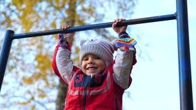 Übung in der Frischluft Ein kleiner Junge, der eine Übung auf der horizontalen Stange tut Bäume, die noch mit etwas goldenen Farb stock footage