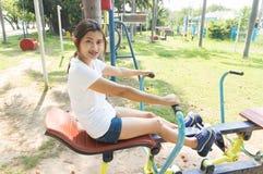 Übung der jungen Frau mit Rudermaschine im Park stockbild