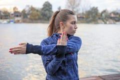 Übungen der jungen Frau durch den Fluss Lizenzfreie Stockbilder