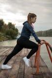 Übungen der jungen Frau durch den Fluss Stockbild