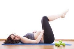 Übungen der schwangeren Frau der Junge auf der Matte Stockfotos