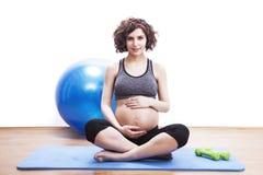 Übungen der schwangeren Frau der Junge auf der Matte Stockbilder