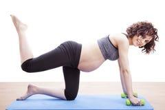Übungen der schwangeren Frau der Junge auf der Matte Lizenzfreies Stockbild