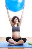 Übungen der schwangeren Frau der Junge mit dem Ball Lizenzfreie Stockbilder