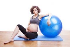 Übungen der schwangeren Frau der Junge mit dem Ball Lizenzfreies Stockbild