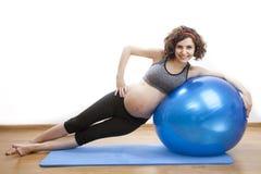 Übungen der schwangeren Frau der Junge mit dem Ball Lizenzfreie Stockfotos