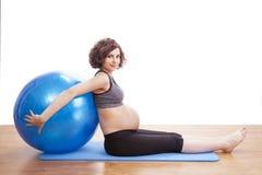 Übungen der schwangeren Frau der Junge mit dem Ball Stockfoto