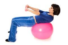 Übungen mit Dumbbells auf einer gymnastischen Kugel Stockbild