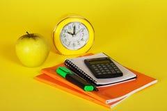 Übungsbücher, ein Notizblock, Taschenrechner und Apfel Stockbilder