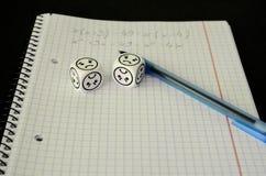 Übungsbuch mit mathematischer Gleichung und würfelt mit traurigem Gesicht Lizenzfreie Stockfotos