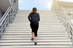 Übungsfrau, die allein herauf Treppe läuft Stockbild
