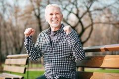 Üppige Anhörungsgute nachrichten des älteren Mannes lizenzfreie stockbilder