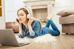 Üppige blonde Frau, die Musik hört Lizenzfreies Stockbild